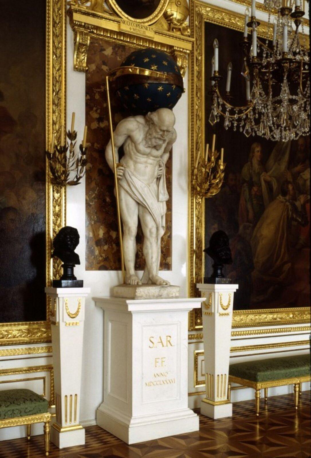 """Ilustracja przedstawia dzieło Giacomo Monaldiego """"Chronos"""". Ukazuje posąg nagiego starca dźwigającego na barkach gwiaździsty glob, na którego ruchomej obręczy, służącej jako tarcza zegara, trzymaną wręku kosą wskazuje godziny odmierzane mechanizmem ukrytym wewnątrz kuli, stoi na postumencie znapisem: S.A.R. - F.F. Anno MDCCLXXXVI (Stanislaus Augustus Fieri Fecit 1786)."""