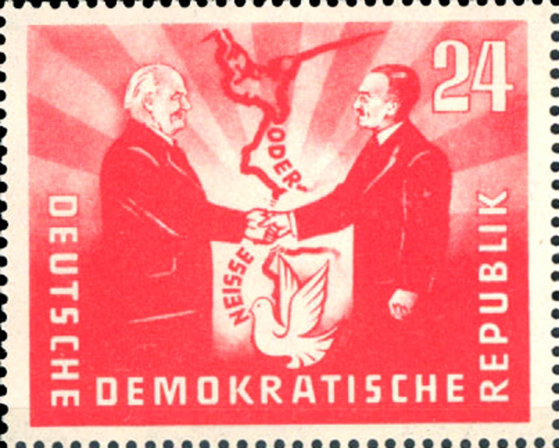 Znaczek pocztowy. Na nim dwie ściskające sobie ręce postaci. Pomiędzy nimi widać rzeki Odre iNysę, tworzące granicę, oraz białego ptaka. Na znaczku napis po niemiecku: Niemiecka Republika Demokratyczna.