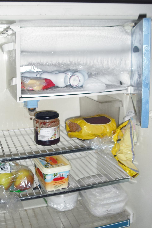 Zdjęcie ukazujące otwartą, oblodzoną lodówkę.