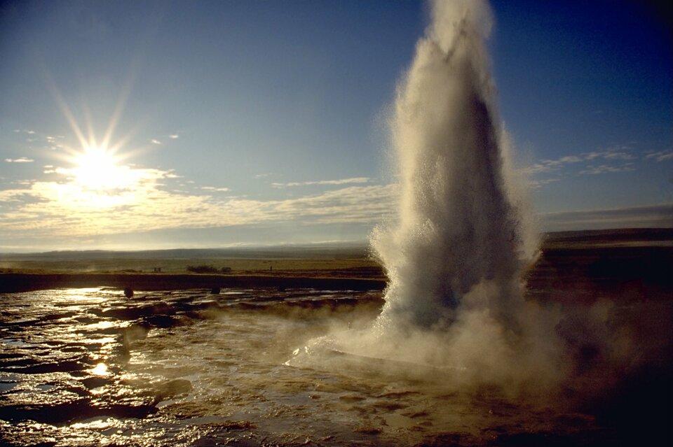 Na zdjęciu słup wody unoszący się nad zagłębieniem wypełnionym wodą. Zachodzące słońce.