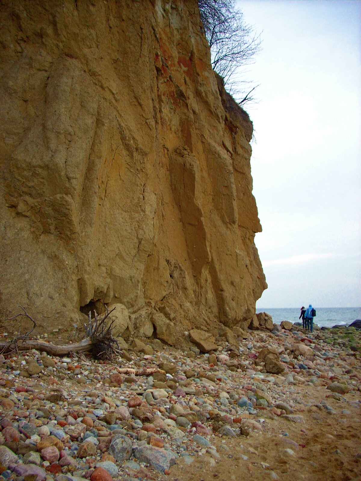 Na zdjęciu nadmorski klif. Wysoka, bardzo stroma ściana skalna. Ujej podstawy oderwane fragmenty ściany, kamienie. Wtle morze. Ludzie na plaży.