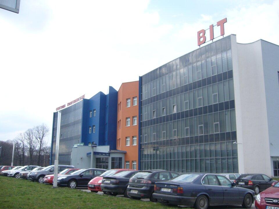 Na zdjęciu nowoczesne budynki biurowe. Przed nimi zaparkowane samochody.