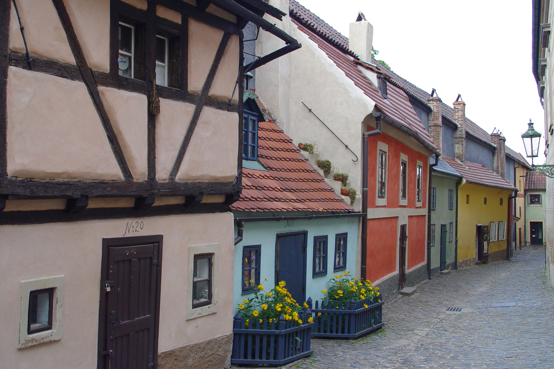 Zdjęcie przedstawia letni widok Złotej Uliczki wPradze. Jest to miejsce, wktórym mieli zamieszkiwać alchemicy izłotnicy na przełomie XVI iXVII wieku. Uliczka zabudowana jest kolorowymi ibardzo małymi domkami. Wwąskim kadrze zdjęcie mieści się sześć tradycyjnych budynków mieszkalnych, zktórych każdy ma inny kolor. Patrząc od lewej: brązowy, turkusowy, czerwony, morski, żółty, jasnożółty ijasnozielony.