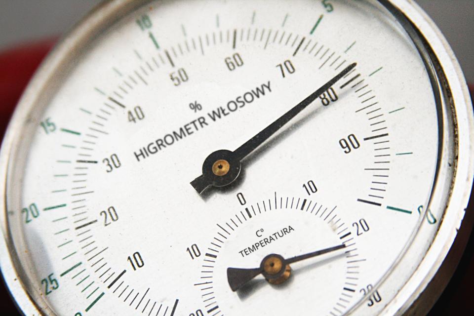 Zdjęcie przedstawia przyrząd mierniczy zwany higrometrem. Przyrząd ma kształt okrągłej tarczy zegara. Wokół tarczy znajduje się skala liczbowa od zera do stu. Skala liczbowa wskazuje wartość wilgotności wprocentach. Wcentrum znajduje się wskazówka, która obracając się wskazuje wilgotność na skali. Wdolnej części znajduje się mała skala liczbowa termometru. Mała wskazówka obraca sie iwskazuje wysokość temperatury wskali Celsjusza.