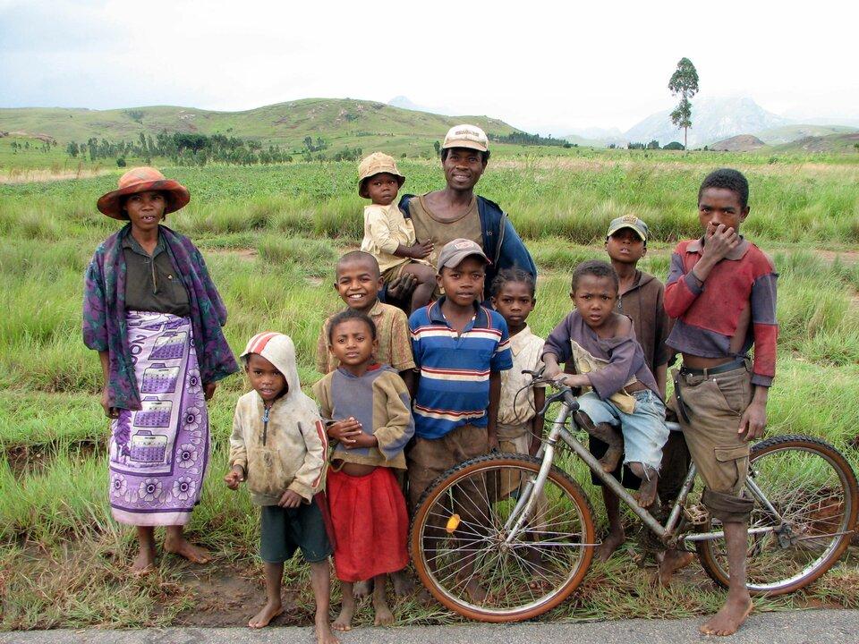 Na zdjęciu wielodzietna rodzina. Stoją na dworze, jedno dziecko na rowerze.