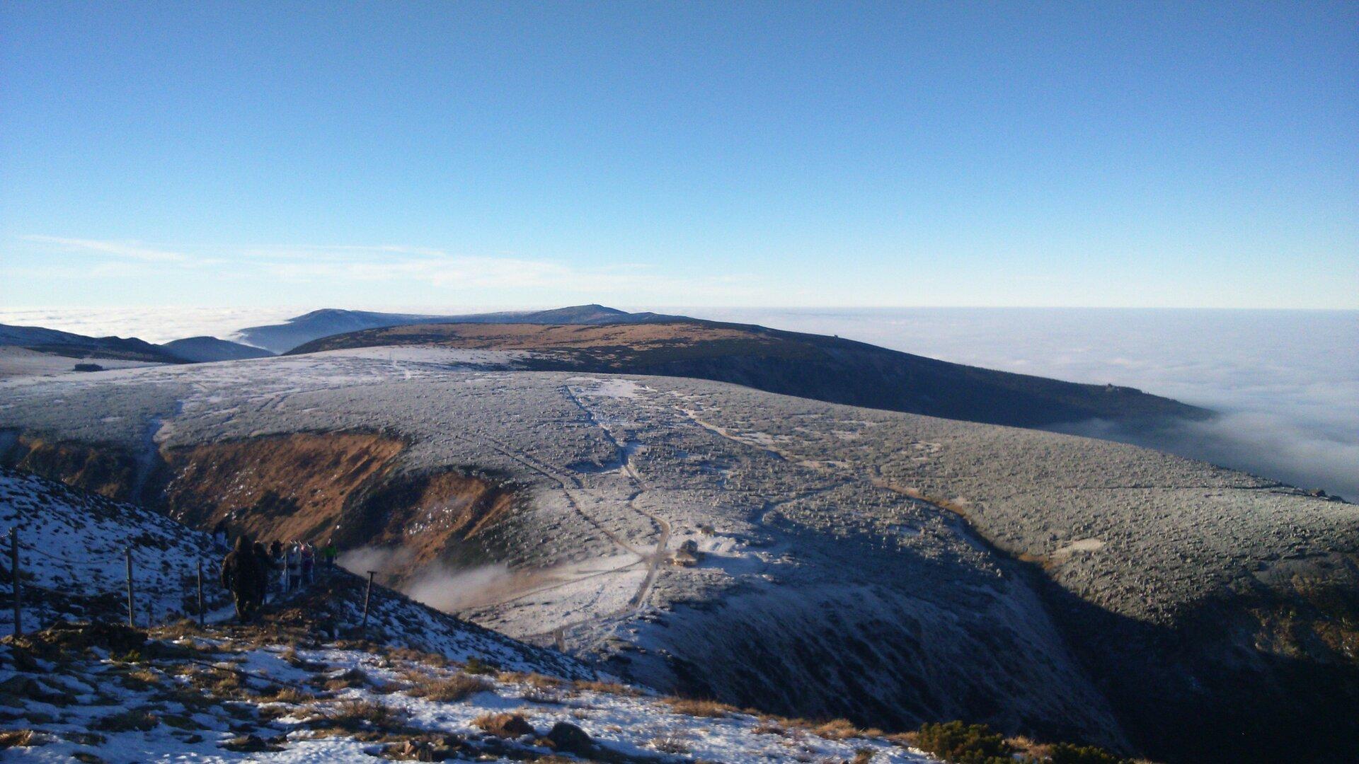 Na zdjęciu rozległe pasmo łagodnych gór, szczyty ośnieżone.