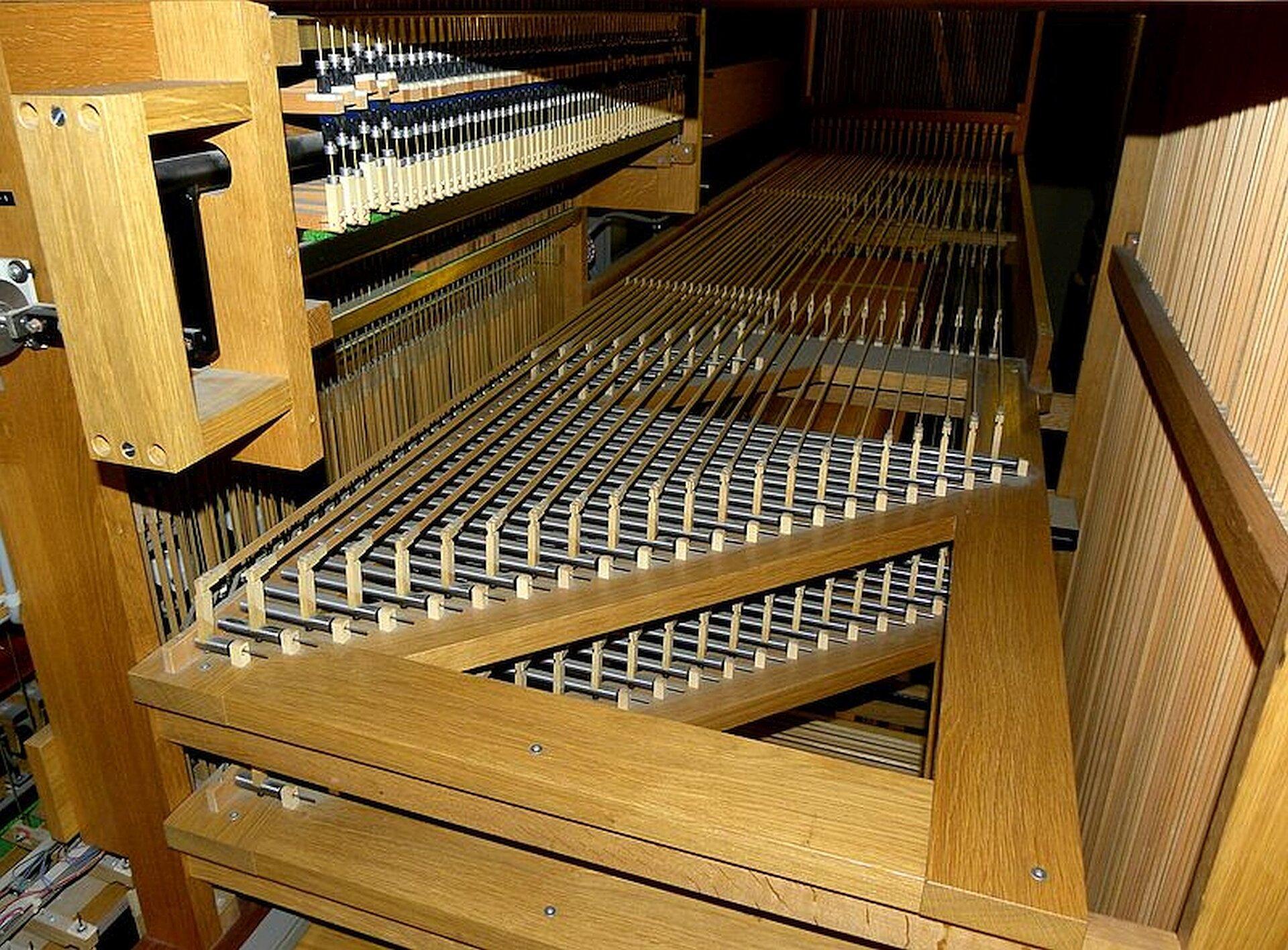 Zdjęcie podpisane: elementy mechanicznej traktury gry - tzw. mechanizm wałkowy. Na zdjęciu widoczny jest mechanizm wykonany zdrewna imetalu. Widać wiele równoległych metalowych połączeń uruchamianych przez młoteczki. Zadaniem tych połączeń jest przekazywanie ruchu klawiszy naciskanych przez organistę na ruch wentyli wpuszczających powietrze do piszczałek.
