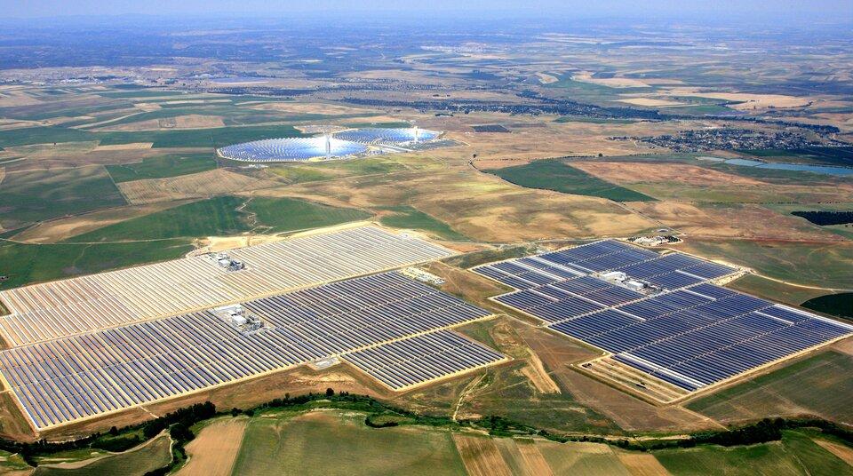 Fotografia zlotu ptaka. Przedstawiony rozległy płaskowyż, szachownica pól uprawnych, terenów zielonych. Na pierwszym planie wielkie obszar pokryte przez kolektory słoneczne.