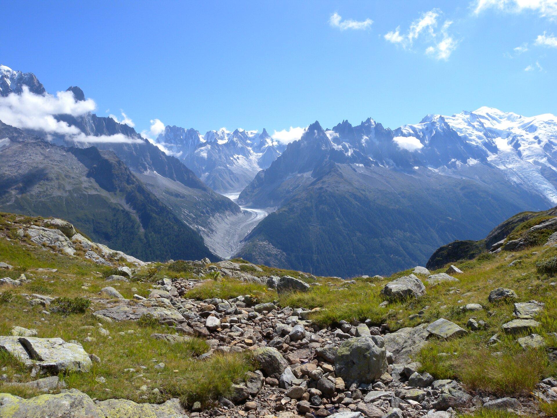 Na zdjęciu wysokie góry, ośnieżone szczyty pozbawione roślinności, na pierwszym planie teren porośnięty trawą, kamienie.