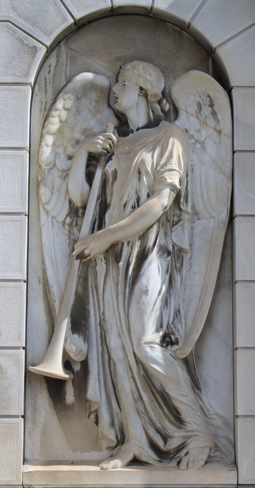 Ilustracja przedstawia detal rzeźbiarski zmauzoleum rodziny Pirkershausen. Na zdjęciu znajduje się rzeźba anioła odużych skrzydłach, wpowłóczystej szcie zdługą trąbą wrękach. Ustawiona wkontrapoście postać lekko wychyla się wprawą stronę, twarz ujęta jest zprofilu. Rzeźba wpisana jest wpółokrągłą wnękę. Anioł skrzydłami iplecami przylega do ściany.