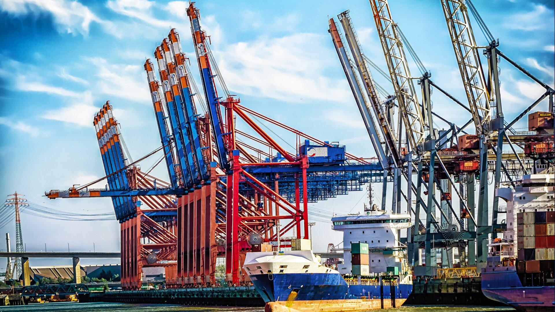 Zdjęcie przedstawia port morski. Na fotografii widać dźwigi wkolorze szarym iczerwono-niebieskim. Wcentrum ilustracji znajduje się statek średniej wielkości, transportujący towary. Po prawej stronie znajduje się większy statek załadowany kontenerami. Woddali widać wiadukt.