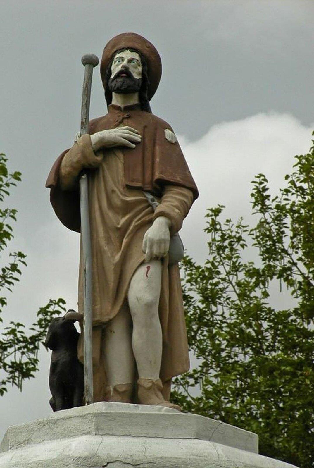 lustracja przedstawia figurę świętego Rocha. Święty wdłoni trzyma laskę, aobok niego siedzi pies. Na głowie ma brązowe nakrycie iszatę wtakim samym kolorze.