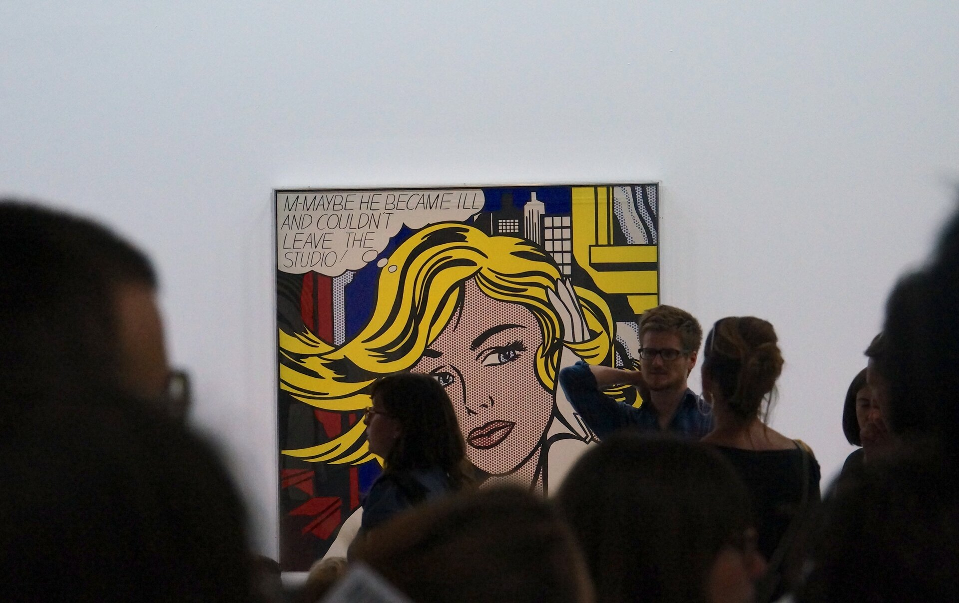 """Ilustracja przedstawia zdjęcie zgalerii przedstawiające dzieło Roya Lichtensteina """"M-Maybe"""", ukazujące kobietę ożółtych włosach na tle miejskiego pejzażu. Przed dziełem stoi mężczyzna, który opowiada odziele. NA pierwszym planie zgromadzeni są ludzie."""