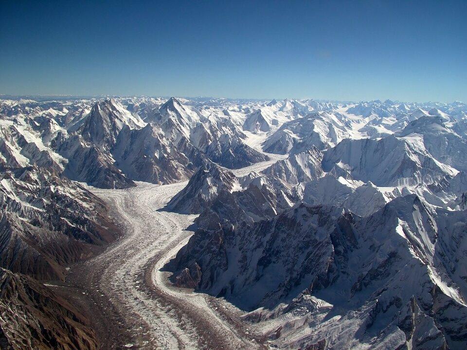 Na zdjęciu krajobraz wysokogórski. Strome góry niemal wcałości pokryte śniegiem. Środkiem doliny płynie lodowiec. Szeroki pas zmrożonego śniegu. Na pierwszym planie biały jęzor nieco zabrudzony ziemią. Wtle niebieskie niebo.