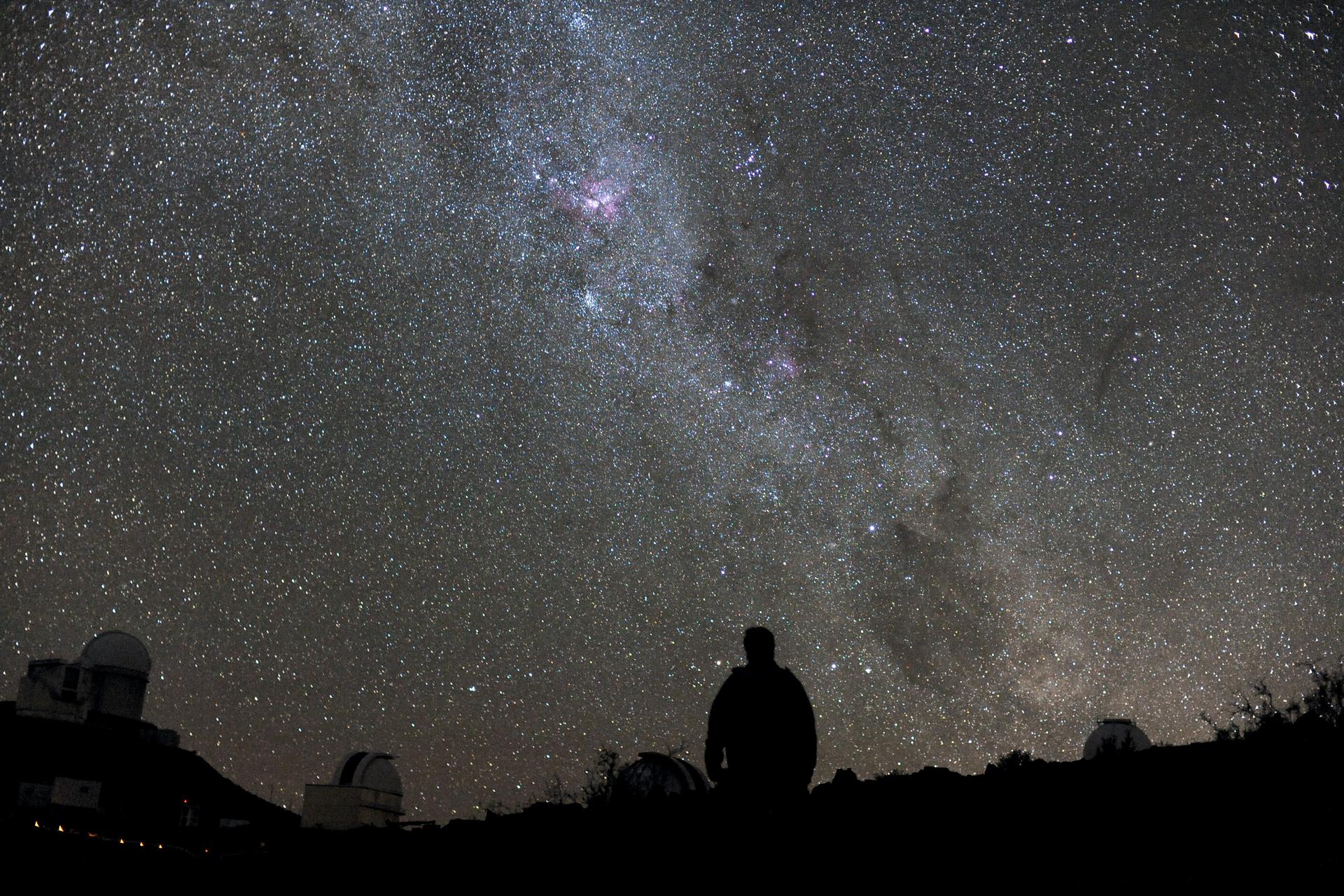 Zdjęcie przedstawia nocne niebo. Udołu fotografii widać zarys podłoża oraz osoby, która stoi po środku. Niebo ciemne, gwieździste.