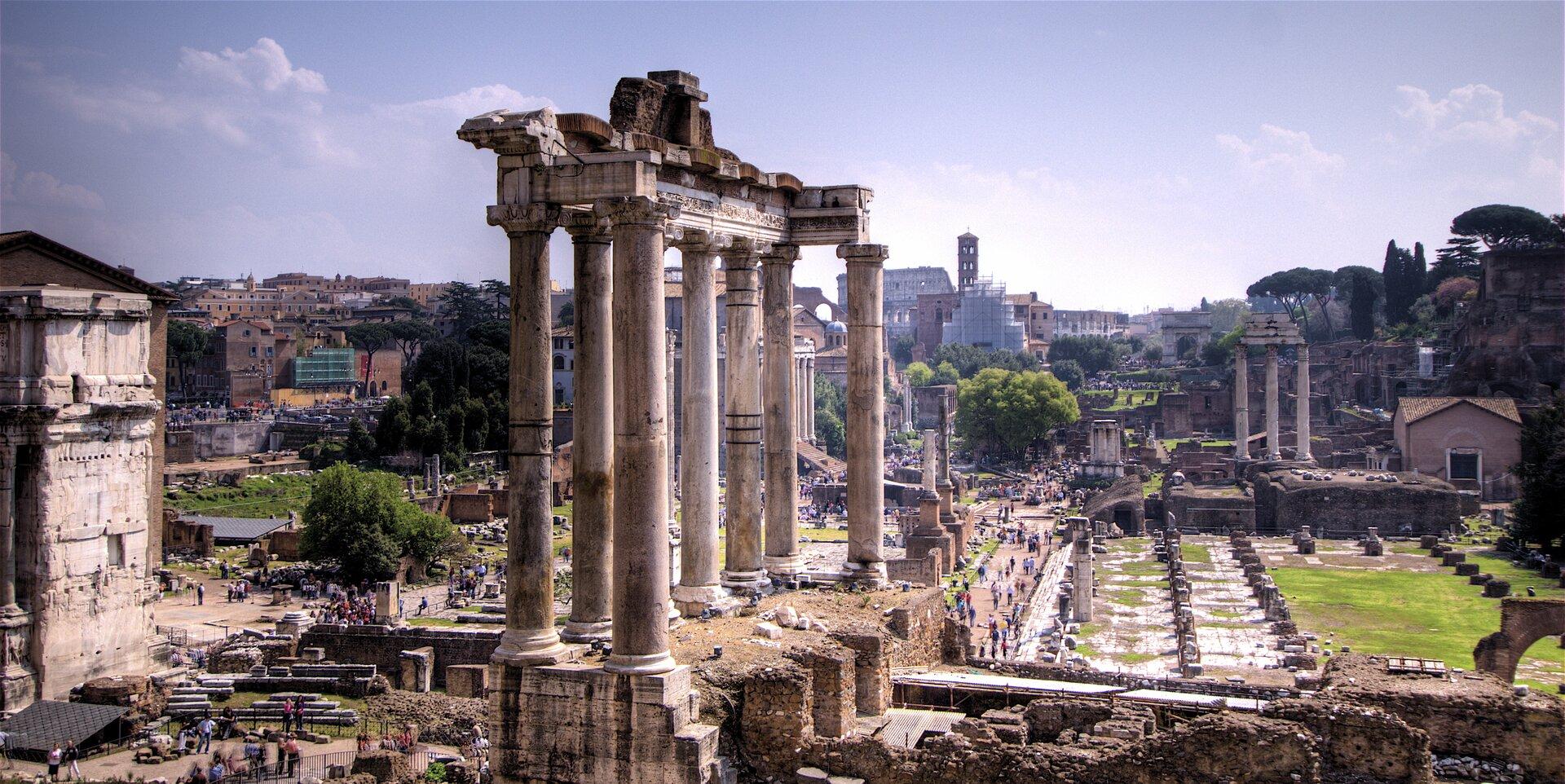 Na zdjęciu rozległy plac, ruiny starożytnych budowli, pozostałości świątyni, kolumny. Dużo osób zwiedzających.