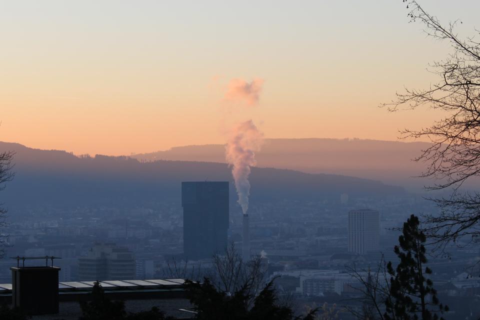 Zdjęcie przedstawiające widok na miasto zoddali, wśrodku miasta widoczny wysoki komin, zktórego unosi się prosto do góry szary dym.