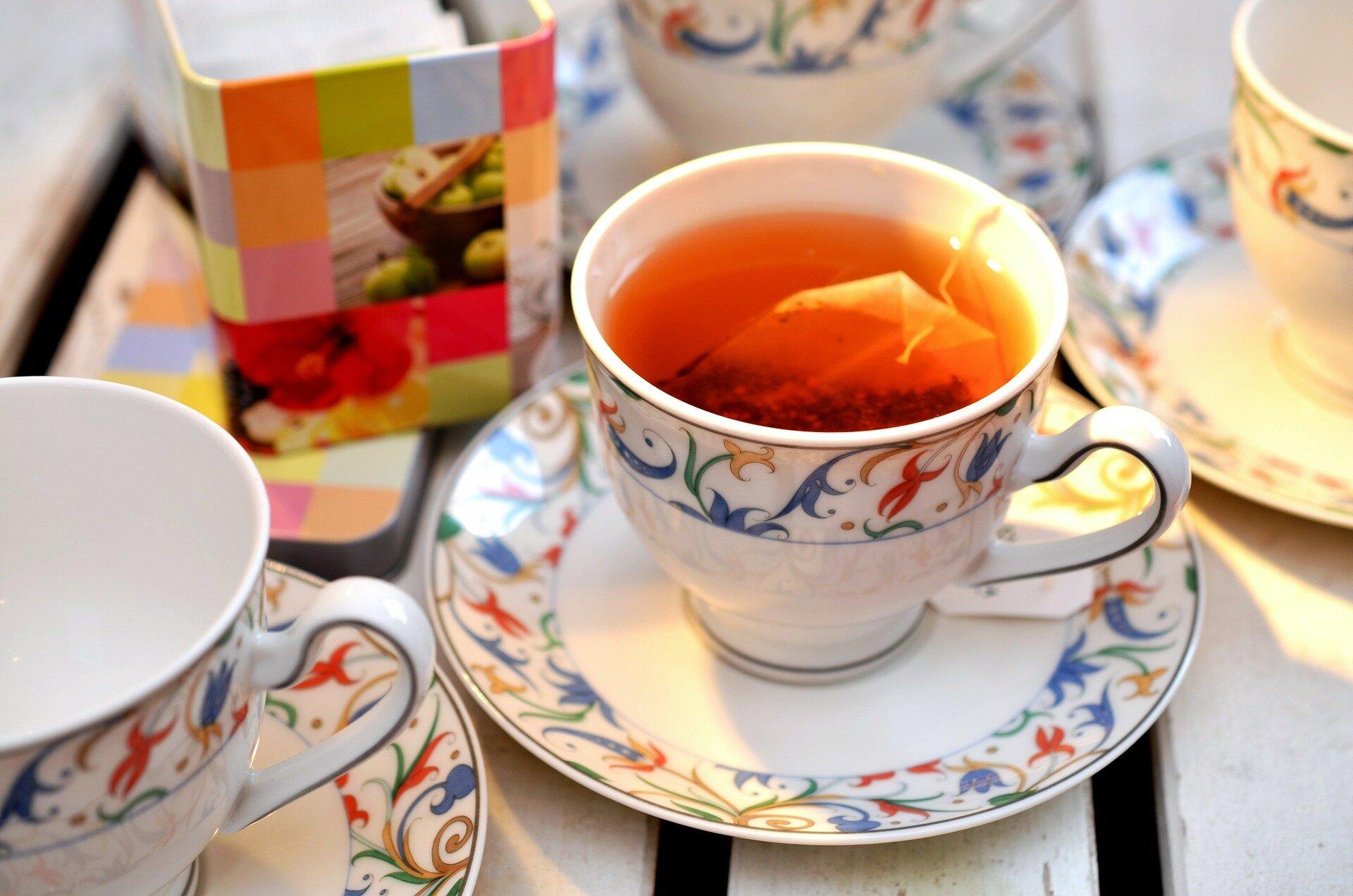 Fotografia prezentuje filiżankę zparzącą się wniej herbatą
