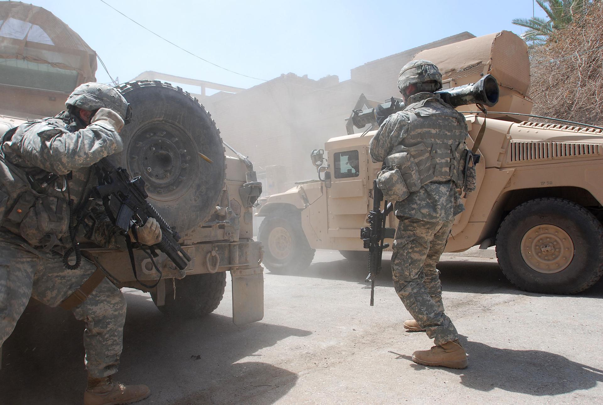 Zdjęcie przedstawia starcie wojska zterrorystami. Słoneczny letni dzień wrejonie Bliskiego Wschodu. Na pierwszym planie dwaj żołnierze. Żołnierze wyposażeni wkarabiny maszynowe iwyrzutnie. Żołnierz po lewej schowany za wozem pancernym. Żołnierz po prawej trzyma wyrzutnię na prawym ramieniu. Po prawej wóz pancerny.