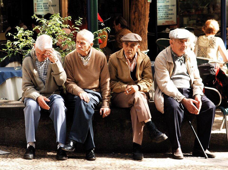 Na zdjęciu czterej mężczyźni wstarszym wieku. Siwe włosy, pomarszczone twarze. Siedzą na murku przed kawiarnią. Jeden trzyma laskę.