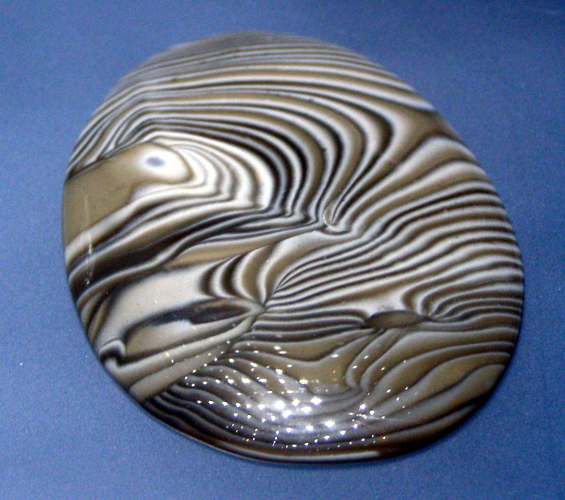 Zdjęcie przedstawia okrągły, gładko oszlifowany kawałek krzemienia pasiastego na niebieskim tle. Kamień cały pokryty jest nieregularnym wzorem składającym się zpowyginanych pasków, naprzemiennie czarnych, białych ibrązowych. Kamień błyszczy, świadczą otym widoczne wdolnej jego części odblaski lampek oświetlających ekspozycję.