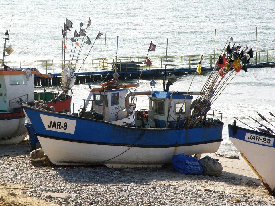 Na zdjęciu kilka kutrów rybackich zacumowanych na plaży. Na kutrach tyczki zchorągiewkami. Wtle mini-molo.