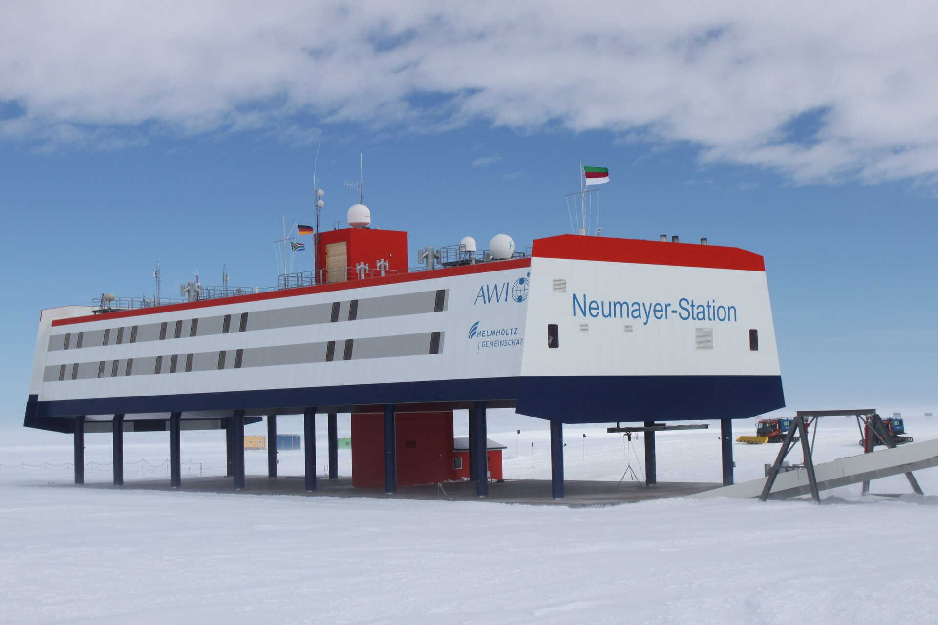 Na zdjęciu płaski budynek posadowiony na palach wbitych wbetonową podstawę. Na dachu flagi. Dookoła ośnieżony teren, pługi śnieżne.