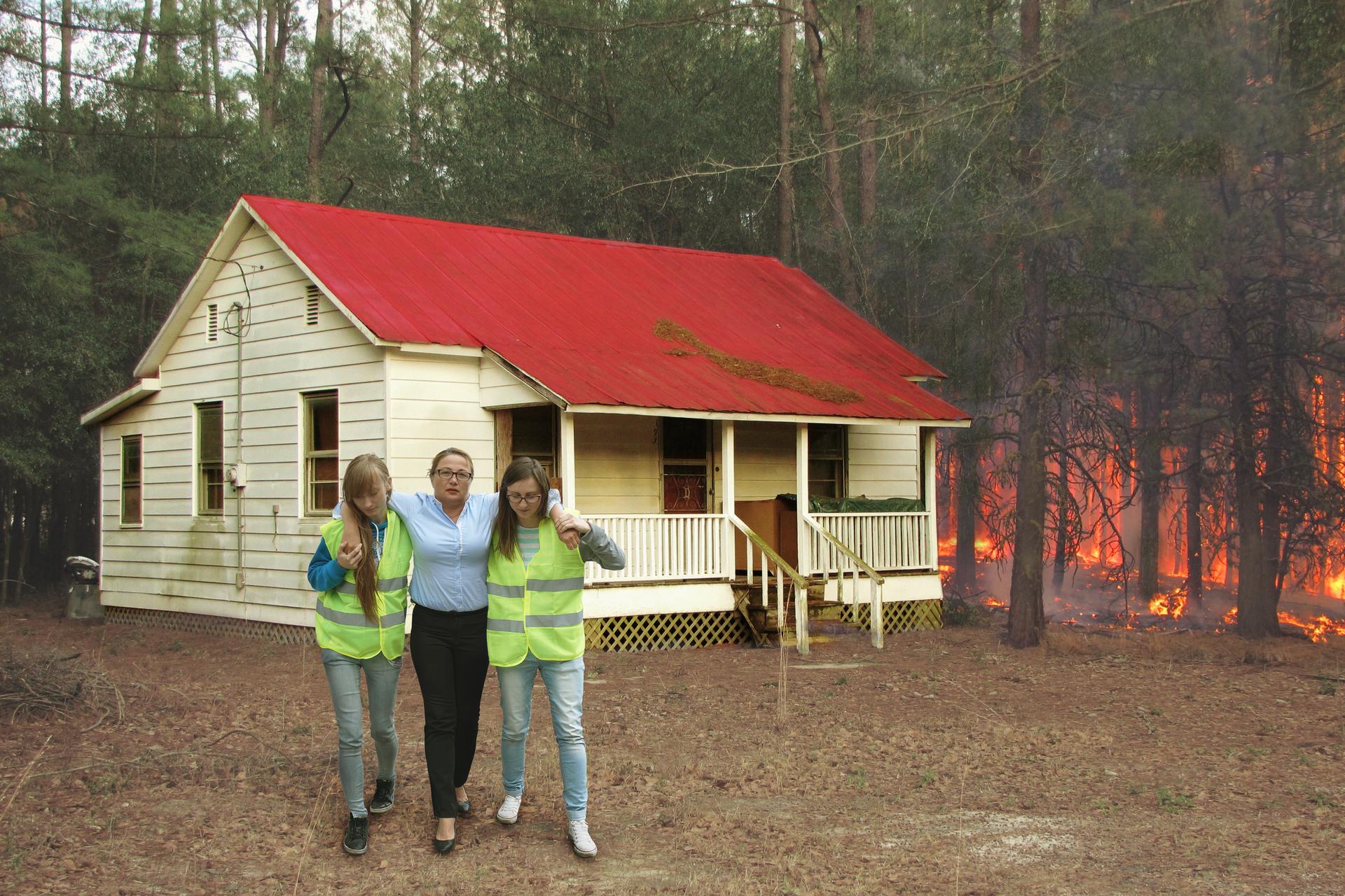 Zdjęcie przedstawia pożar lasu obok budynku mieszkalnego. Wgłębi zdjęcia drewniany budynek jednorodzinny. Za budynkiem palący się gęsty las. Przed budynkiem dwie uczennice pomagają wyprowadzić kobietę zmiejsca zagrożenia. Uczennice ubrane są wkamizelki zodblaskowymi pasami.