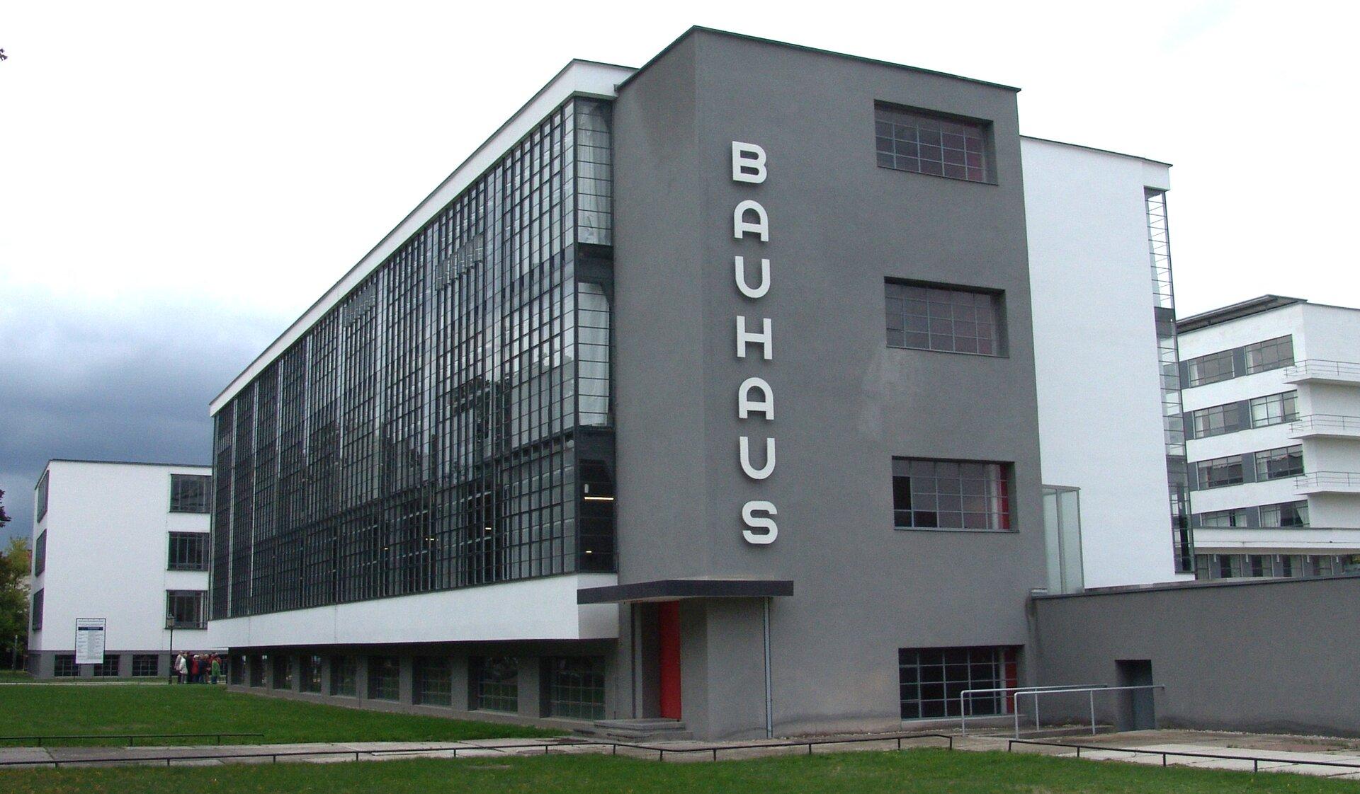 Ilustracja przedstawia kompleks budynków Bauhaus wDessau. Jest to zdjęcie wielokondygnacyjnego budynku wkształcie prostokąta. Dłuższy, front budynku jest przeszklony, ajego bok ciemno-szary zczerwonymi małymi drzwiami udołu. Nad drzwiami znajduje się niewielkie zadaszenie. Przeszklona część jest zakończona zarówno udołu jak iugóry białą fasadą. Pod dolną fasadą widać okna piwniczne. Wpionie na boku elewacji umieszczono biały napis znazwą budynku. Przed budynkiem jest trawnik zchodnikiem prowadzącym do drzwi. Wtle widać dwa białe wielopiętrowe budynki. Na ilustracji umieszczony jest niebieski pulsujący punkt. Po kliknięciu kursorem myszki wpunkt wyświetlą się dodatkowe informacje.