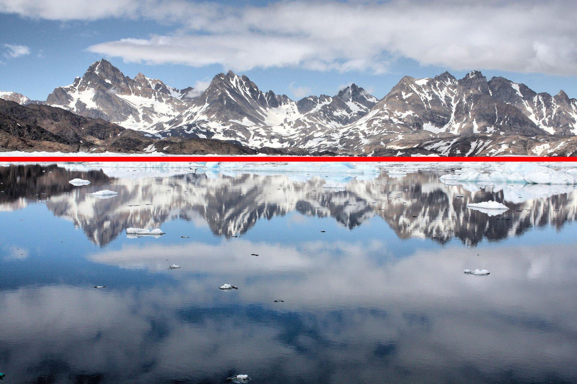 Zdjęcie szczytów górskich położonych nad wodą iodbicie tych gór wwodzie zpoprowadzoną osią symetrii.