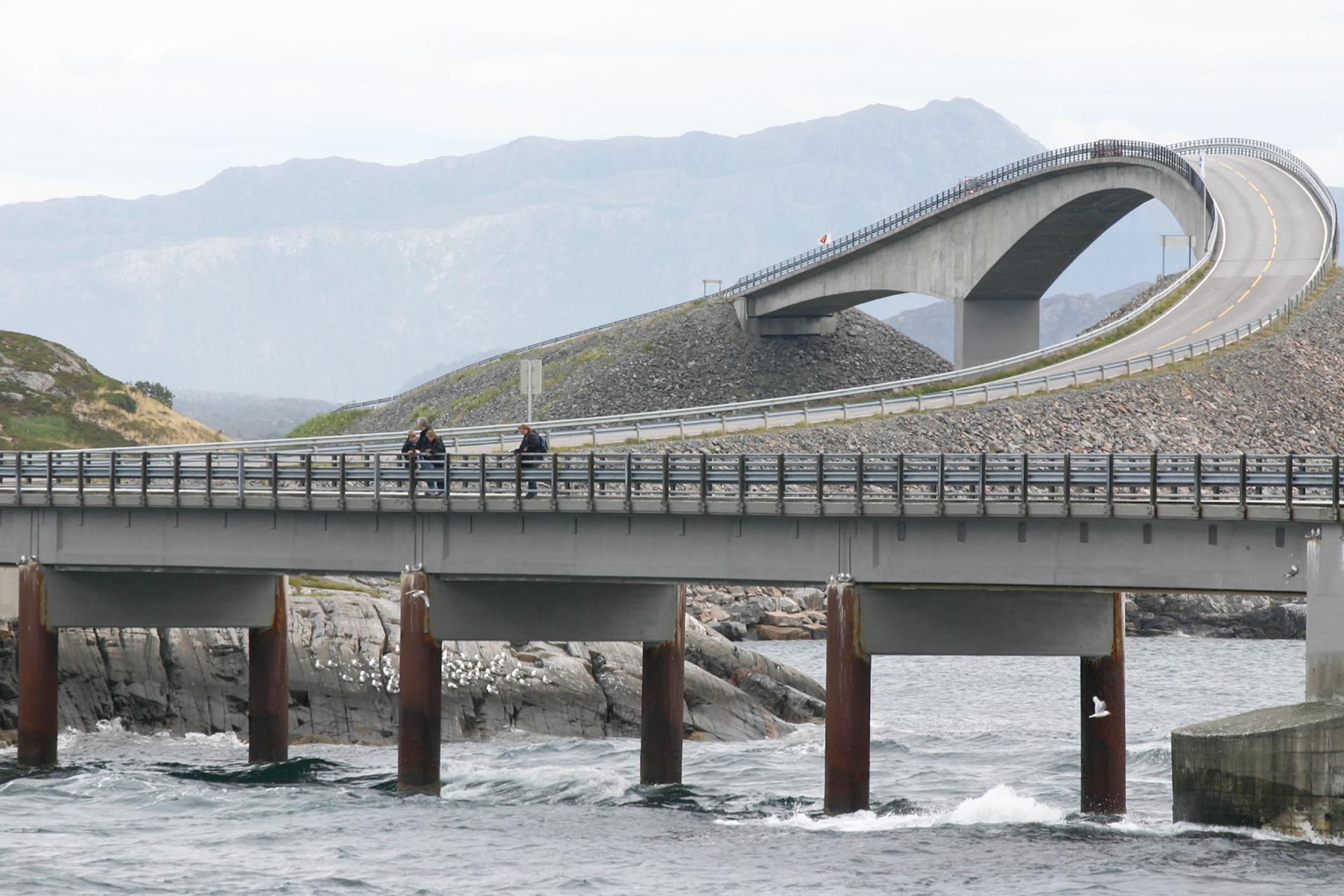 Fotografia prezentuje most łączący brzegi rzeki oraz dwóch wysokich wzniesień.