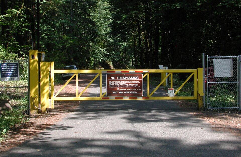Na zdjęciu ogrodzenie zsiatki iżółta brama ztablicą informującą ozakazie wejścia. Na drugim planie drzewa.