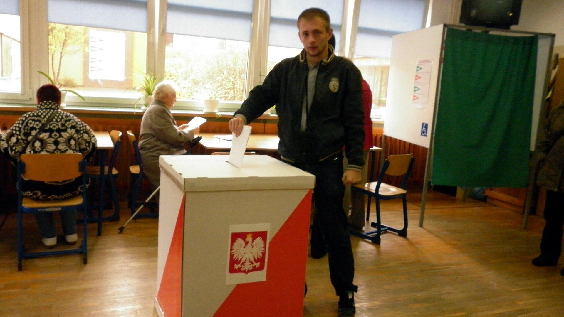 Wybory parlamentarne - mężczyzna przy urnie wyborczej