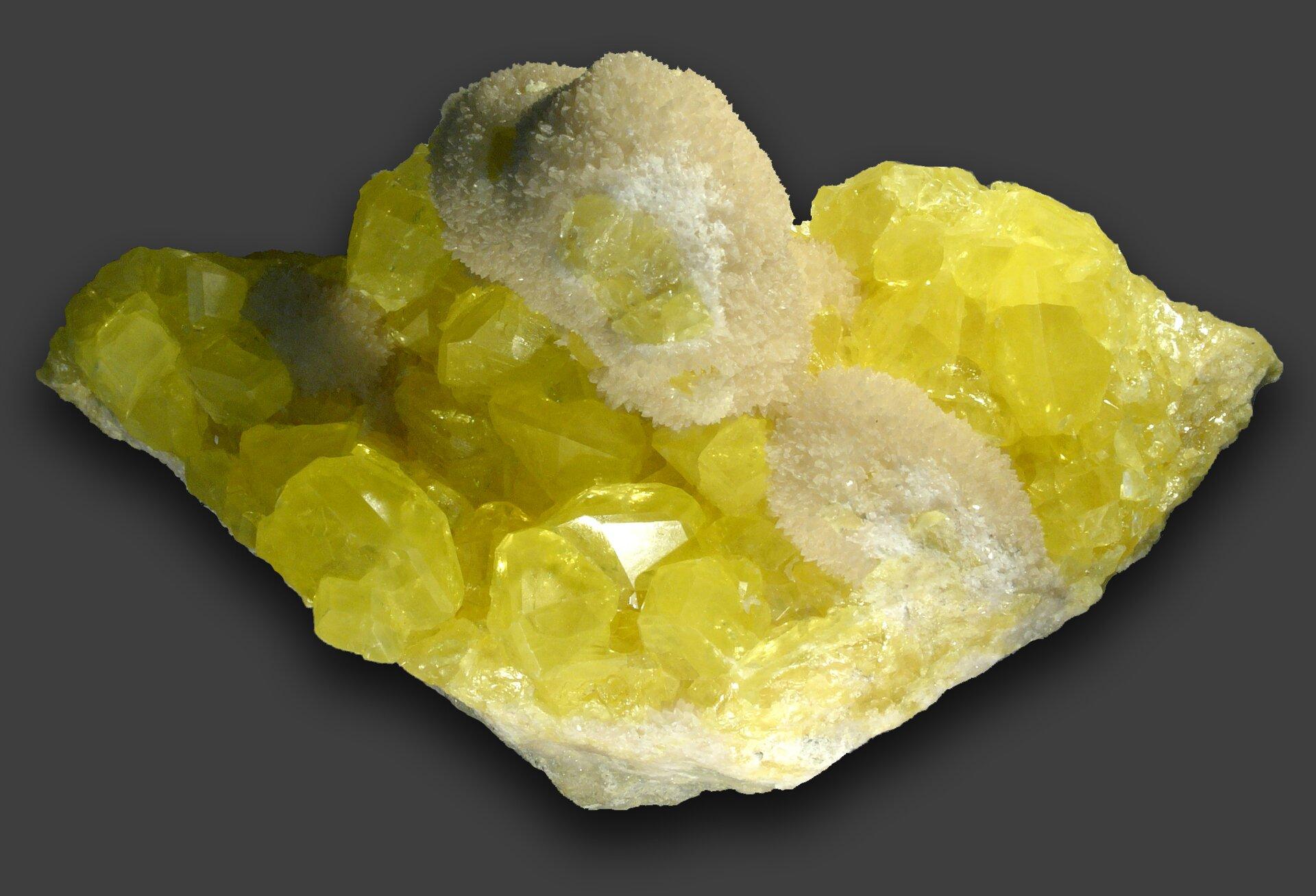 Zdjęcie przedstawia odłamek żółtej siarki składający się zwiększych imniejszych kryształów.