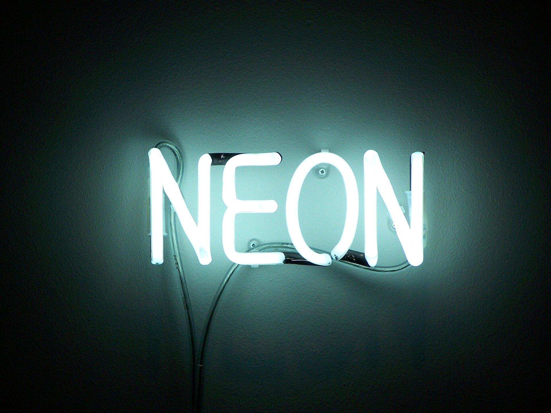 Zdjęcie przedstawia napis świecący NEON ułożony zodpowiednio ukształtowanych wygiętych rurek wypełnionych gazem szlachetnym neonem, na końcach których znajdują się elektrody. Napis świeci intensywną jasnoniebieską barwą rozświetlając najbliższe otoczenie, wtym ścianę do której jest przytwierdzony.