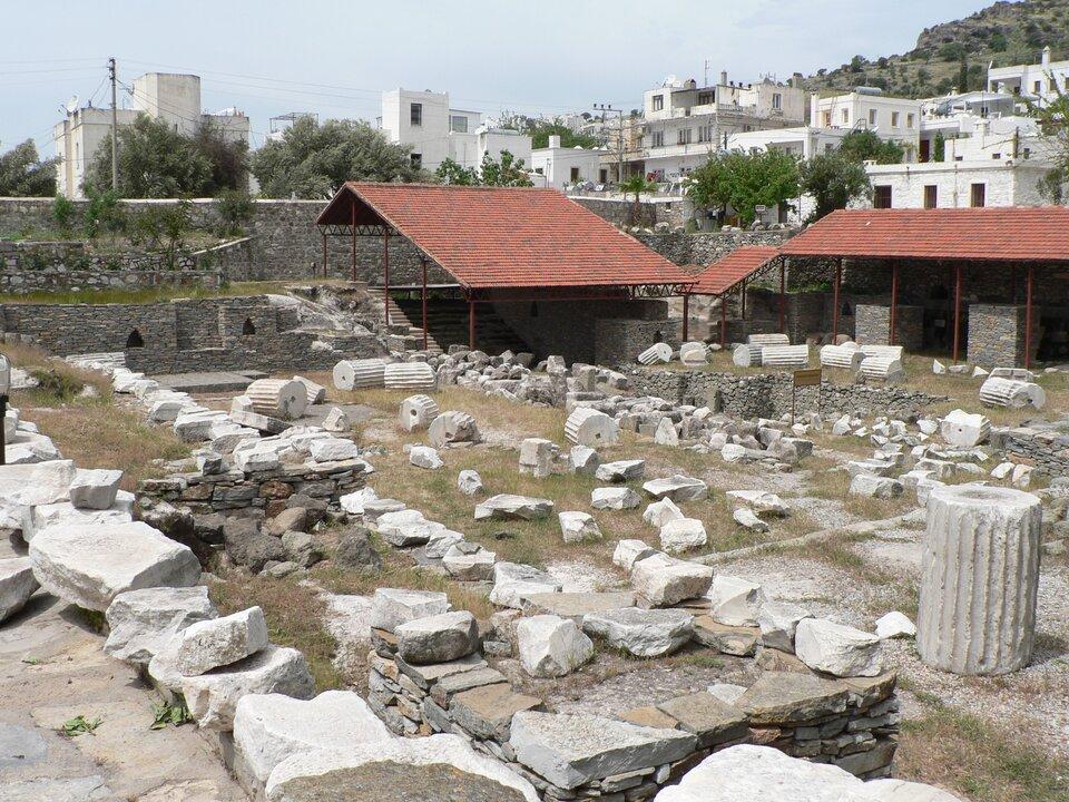 Na zdjęciu pozostałości kolumn, fragmenty fundamentów, kamienie. Wtle dzisiejsza zabudowa.
