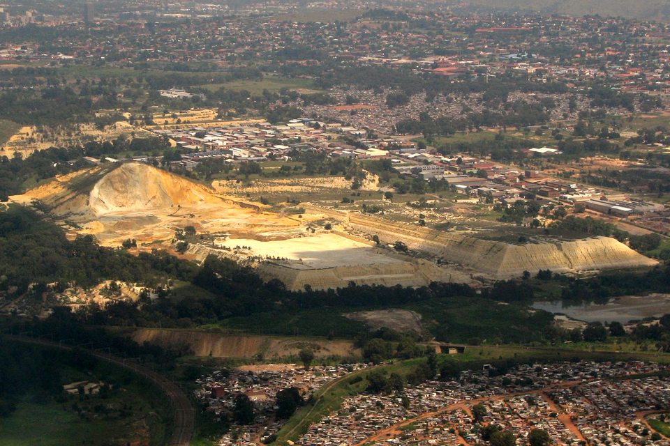 Fotografia przedstawia pejzaż przemysłowy, wujęciu zgóry. Wcentrum znajdują się żółte ikremowe bryły; to hałdy składowanych odpadów. Są ogromne wporównaniu zdomami wokolicy.