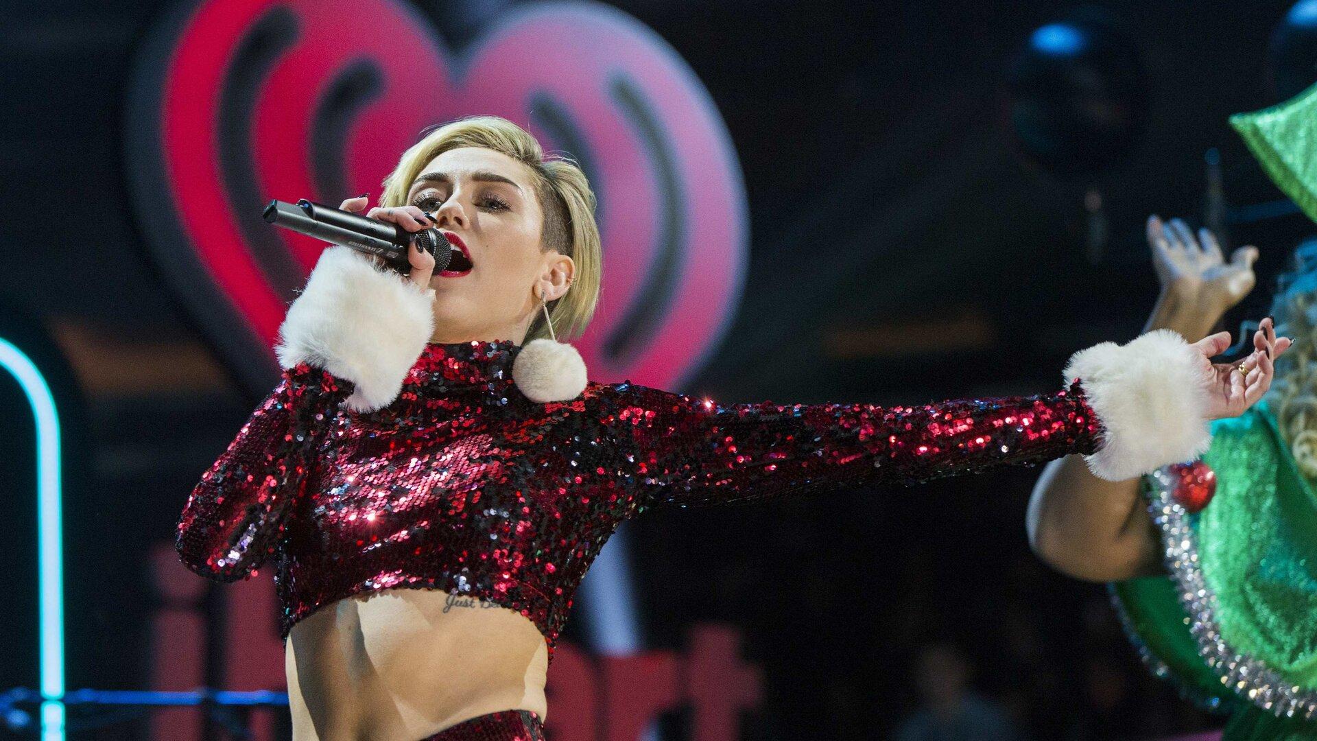 Ilustracja przedstawia koncert muzyki pop. Ukazana jest amerykańska piosenkarka Miley Cyrus. Kobieta ubrana jest  wczerwony, cekinowy kostium.