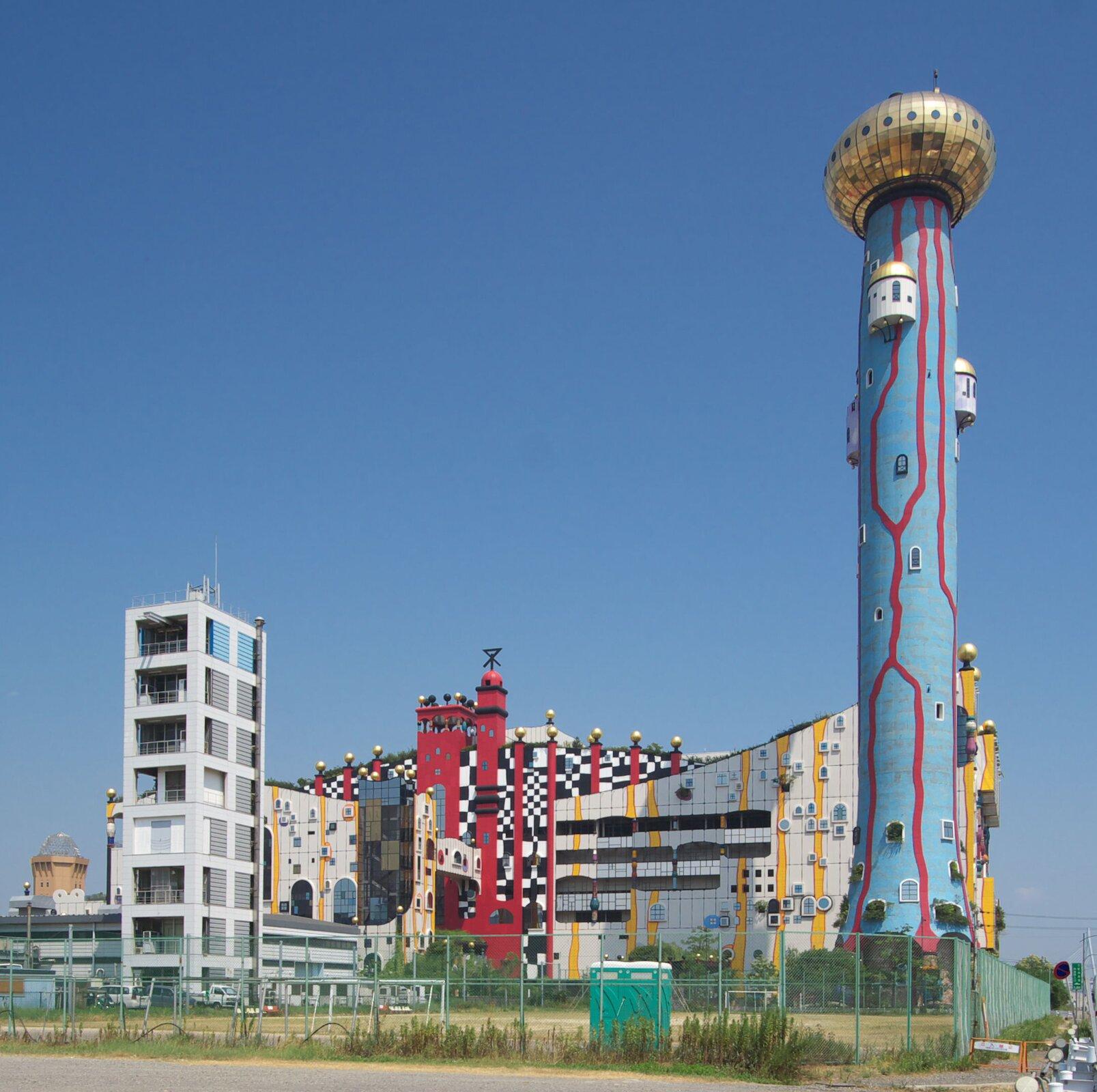 Fotografia przestawia zabudowania spalarni śmieci wOsace(Japonia). Budynki są pomalowane wróżne wzory ikolory. Zprawej wysoki niebieski komin, ozdobiony czerwonymi liniami iokienkami. Ugóry duża, złocista kopuła. Spalarnia wygląda estetycznie.
