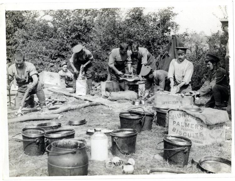 zdjecie przedstawia grupę żolnierzy, są to kucharze,na pierwszym planie widac duże garnki