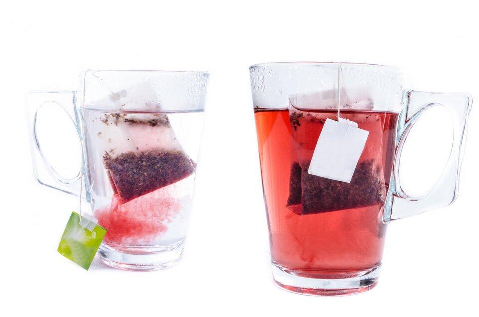 Fotografia przedstawia dwa szklane kubki. Pierwszy wypełniony jest zimną wodą, adrugi ciepłą. Wobu kubkach znajduje się torebka herbaty. Drobiny ztorebki szybciej rozpraszają się wciepłej wodzie.