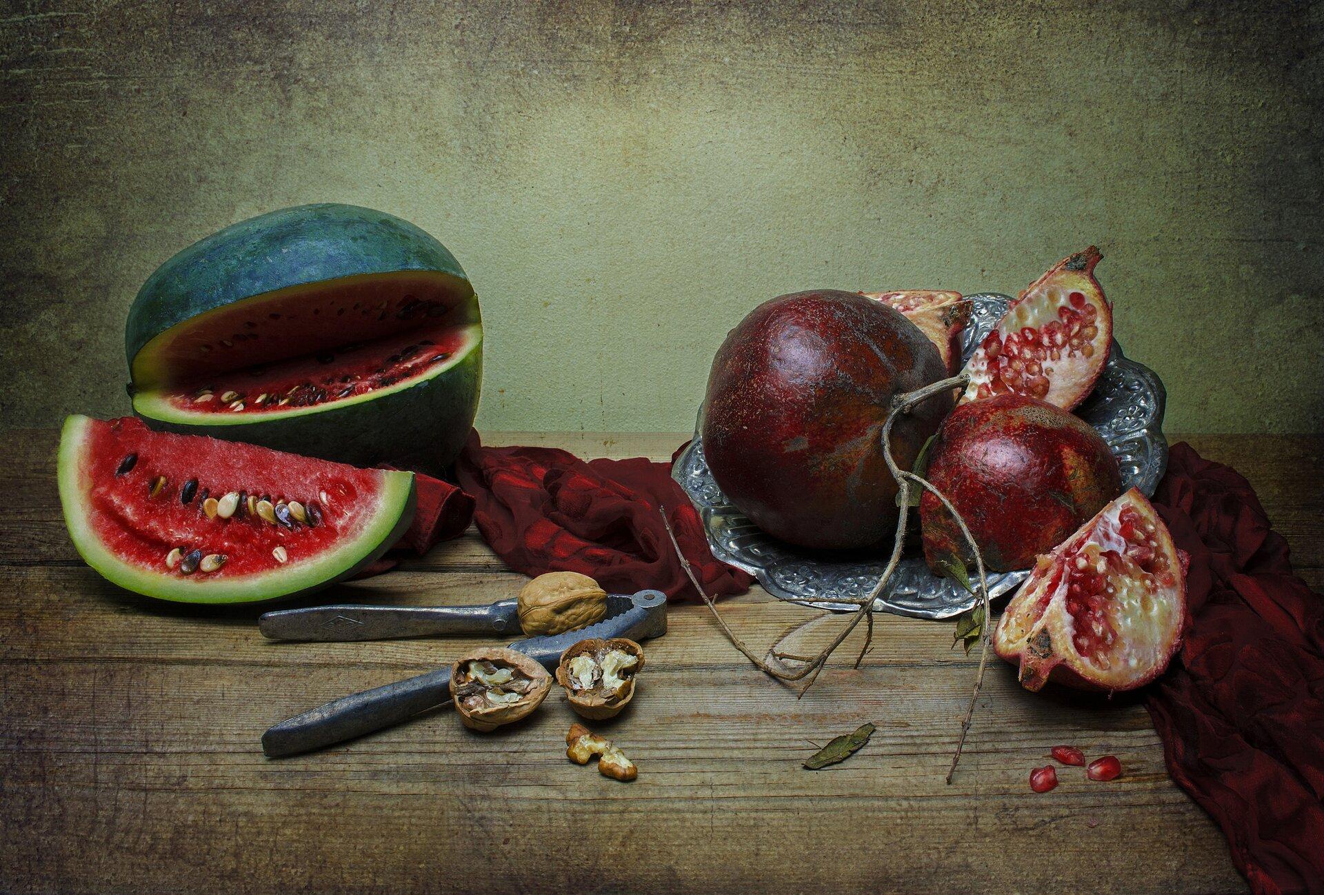 Ilustracja przedstawia zdjęcie martwej natury zowocami. Na drewnianym blacie stołu znajduje się ciemno-zielony arbuz zleżącym przed nim odciętym kawałkiem, oczerwonym miąższu ilicznych dużych pestkach. Po prawej stronie, na czerwonej draperii leży stara, srebrna taca zdrobnym reliefem, na której ułożone są granaty. Obok całego owocu znajdują się ćwiartki, zodkrytymi czerwonymi pestkami, ciasno ułożonymi wjasnym mięsistym miąższu. Trzy znich leży na blacie stołu. Pomiędzy arbuzem agranatami, wcentrum fotografii znajduje się przyrząd do łupania orzechów zjednym całym orzechem oraz drugim rozłupanym obok. Martwa natura ustawiona została na tle zielono-szarej ściany. Fotografia utrzymana jest wwąskiej, ciemnej gamie barw zakcentem ciemnych, soczystych czerwieni.