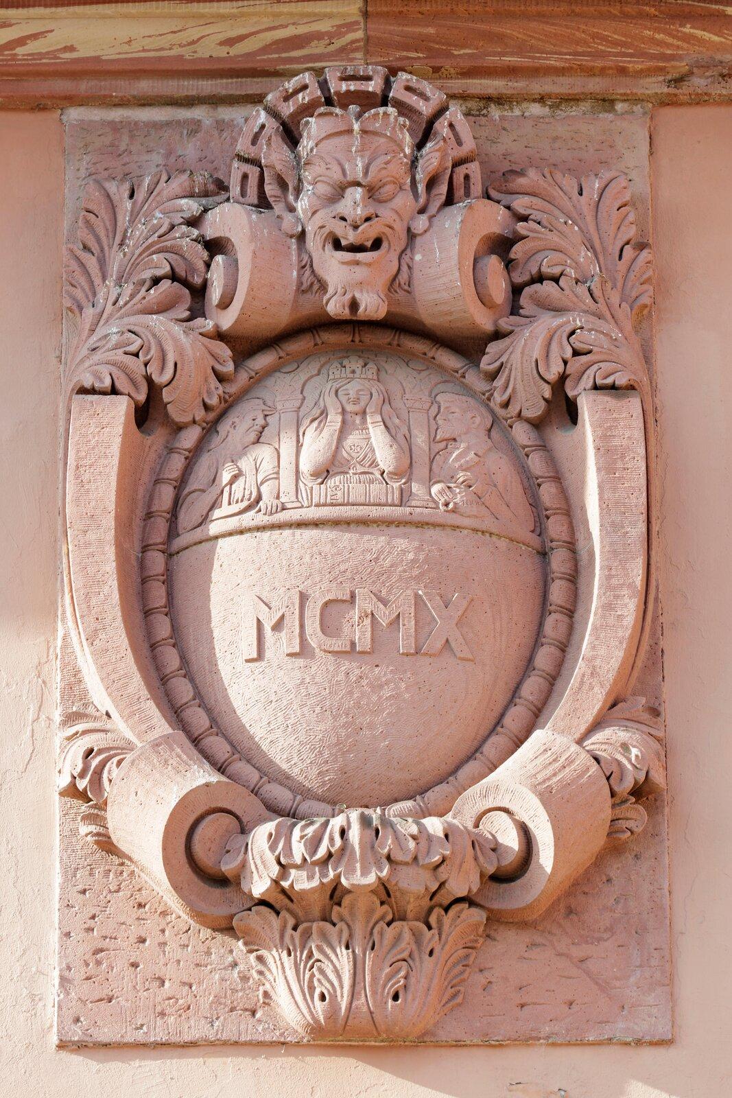 Ilustracja przedstawia ornament – kartusz. Element jest przymocowany do ściany iprzedstawia głowę człowieka zotwartymi ustami. Poniżej głowy znajduje się wypukły element zpłaskorzeźbą oraz znapisem MCMX.