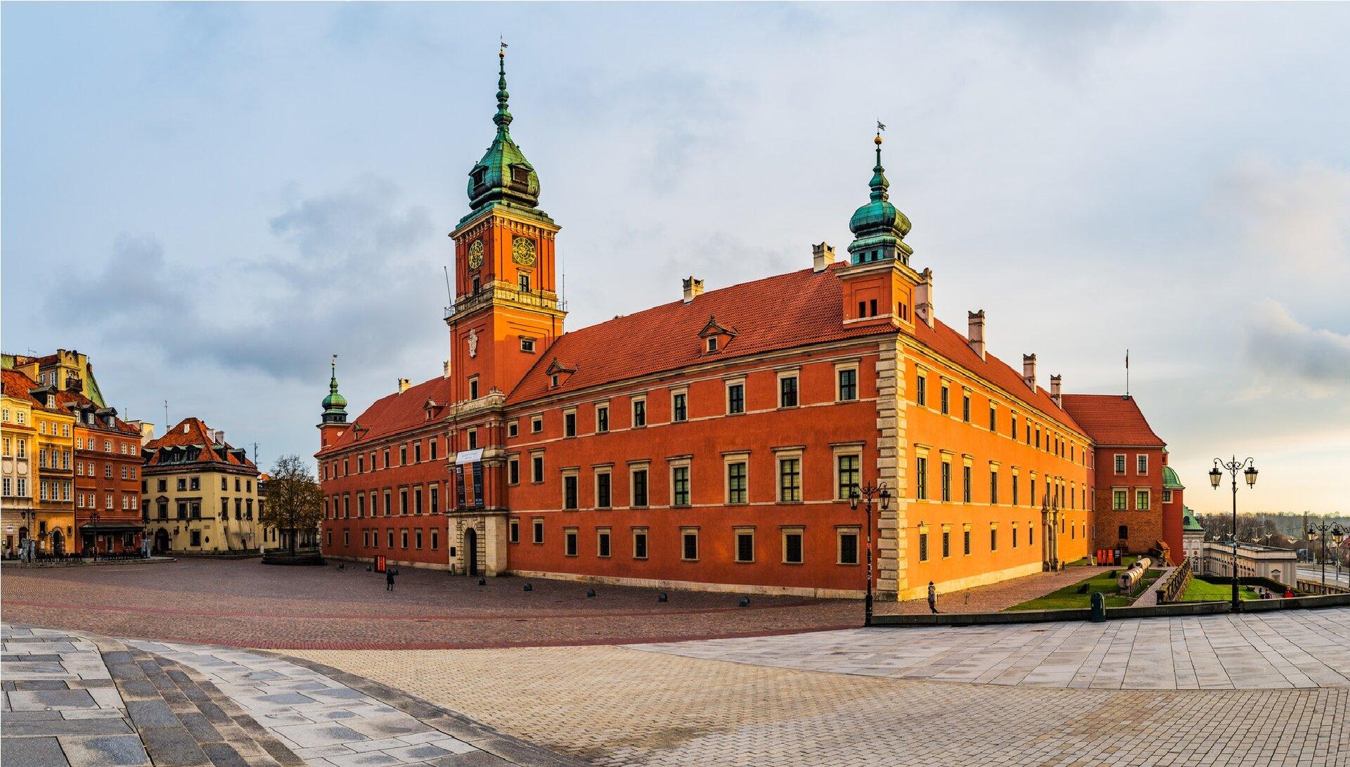 Ilustracja przedstawia Zamek Królewski wWarszawie. Na zdjęciu ukazana jest budowla wstylu barokowo-klasycystycznym, okryta czerwonym, dwuspadowym dachem. Po środku frontowej fasady znajduje się duża wieża zzegarem okryta cebulastą, zielonkawą kopułą zwieńczoną iglicą. Po bokach frontu umieszczone są dwie mniejsze wieże. Wpomalowanej na ceglany kolor elewacji znajdują się trzy rzędy, prostokątnych okien. Budowla ustawiona jest na placu Zamkowym. Po jej lewej stronie znajdują się kamieniczki apo prawej fragment panoramy Warszawy.