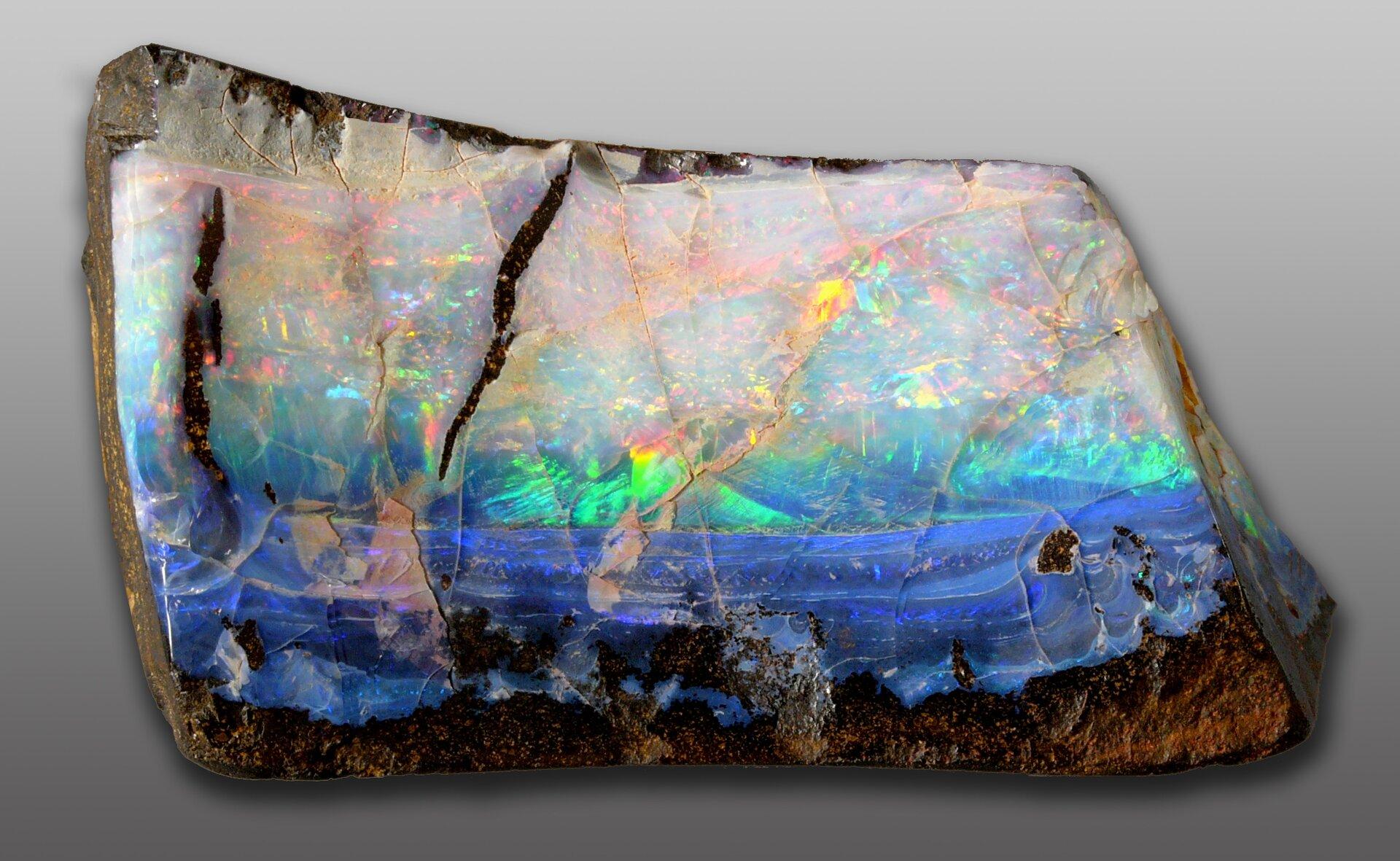 Zdjęcie przedstawia nieoszlifowany opal niebieski wodmianie szlachetnej, czyli opalizującej, co oznacza zmienność barw wzależności od kąta obserwacji.
