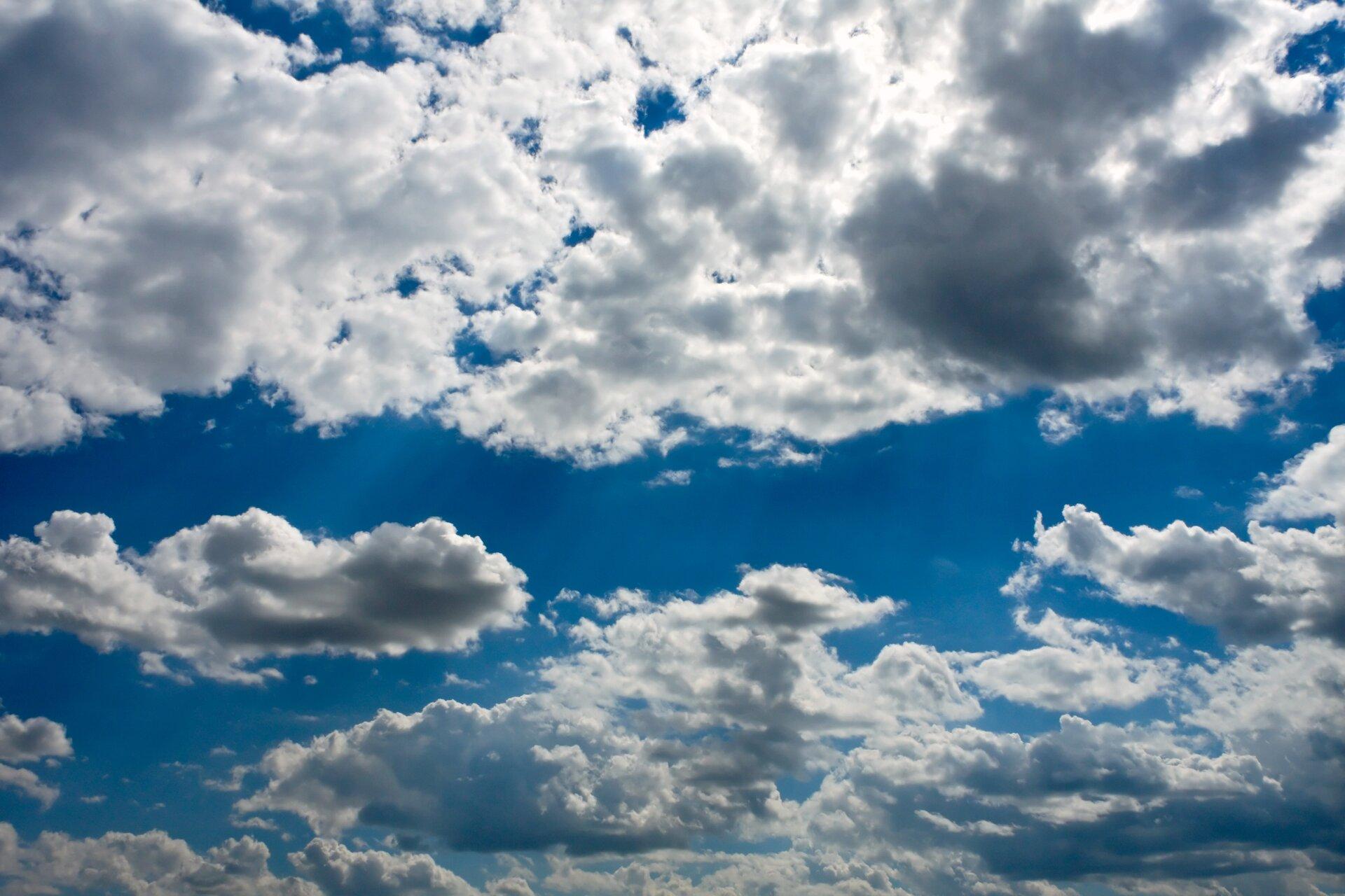 Zdjęcie przedstawia niebieskie niebo częściowo przesłonięte białymi chmurami. Ilustracja stanu skupienia gazowego.
