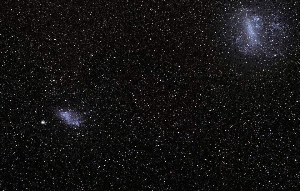 Zdjęcie przedstawia Obłoki Magellana – Wielki iMały – karłowate galaktyki nieregularne.