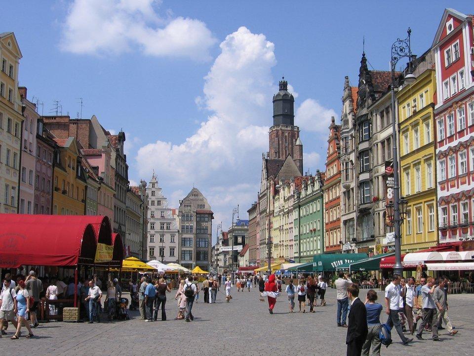 Fotografia prezentująca Rynek miasta Wrocławia. Widoczne kolorowe kamienice oraz wiele osób spacerujących po rynku.