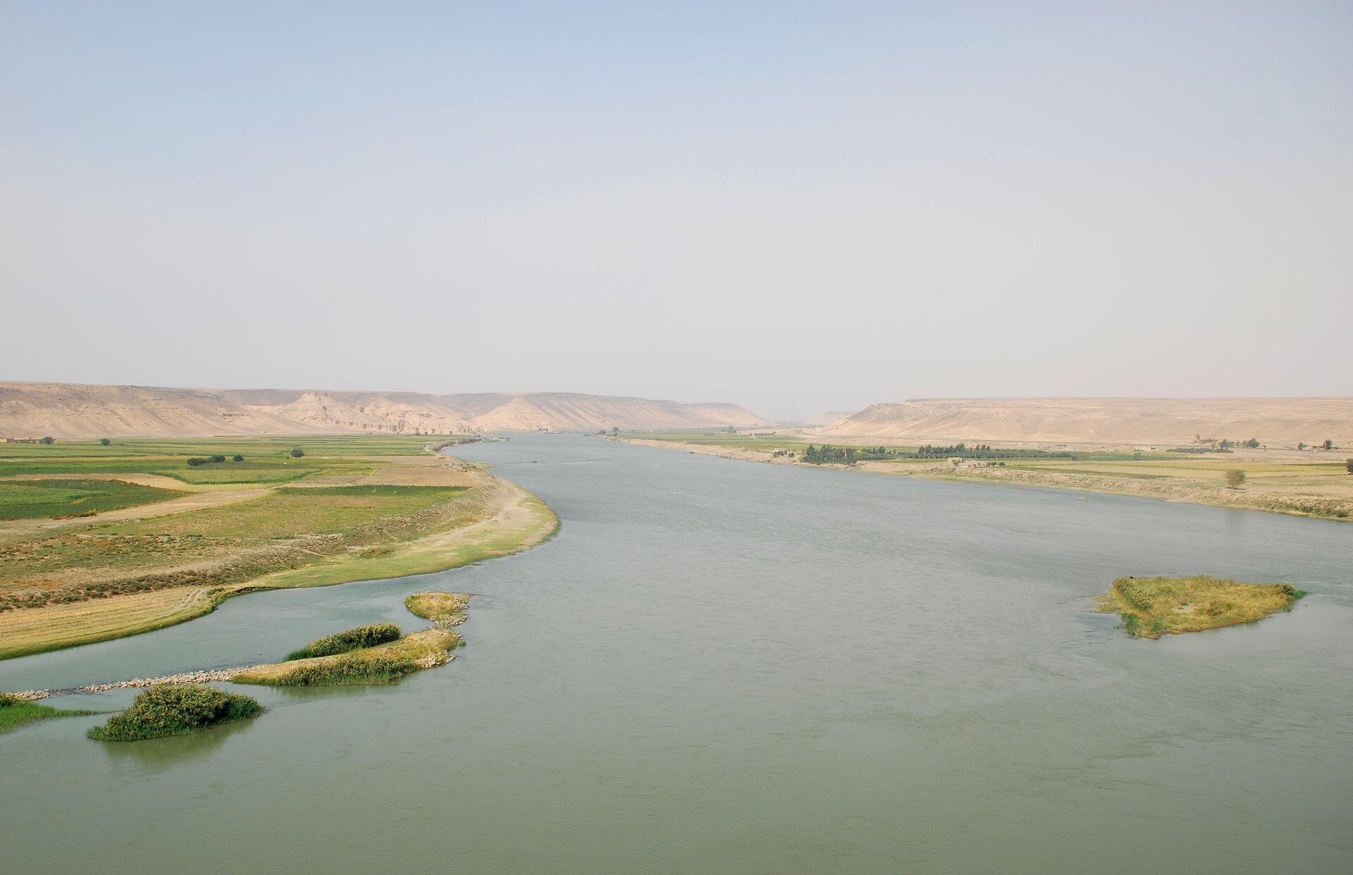 Na zdjęciu szeroka rzeka wrozległym płaskim terenie, płaskie brzegi porośnięte trawą. Wtle góry.
