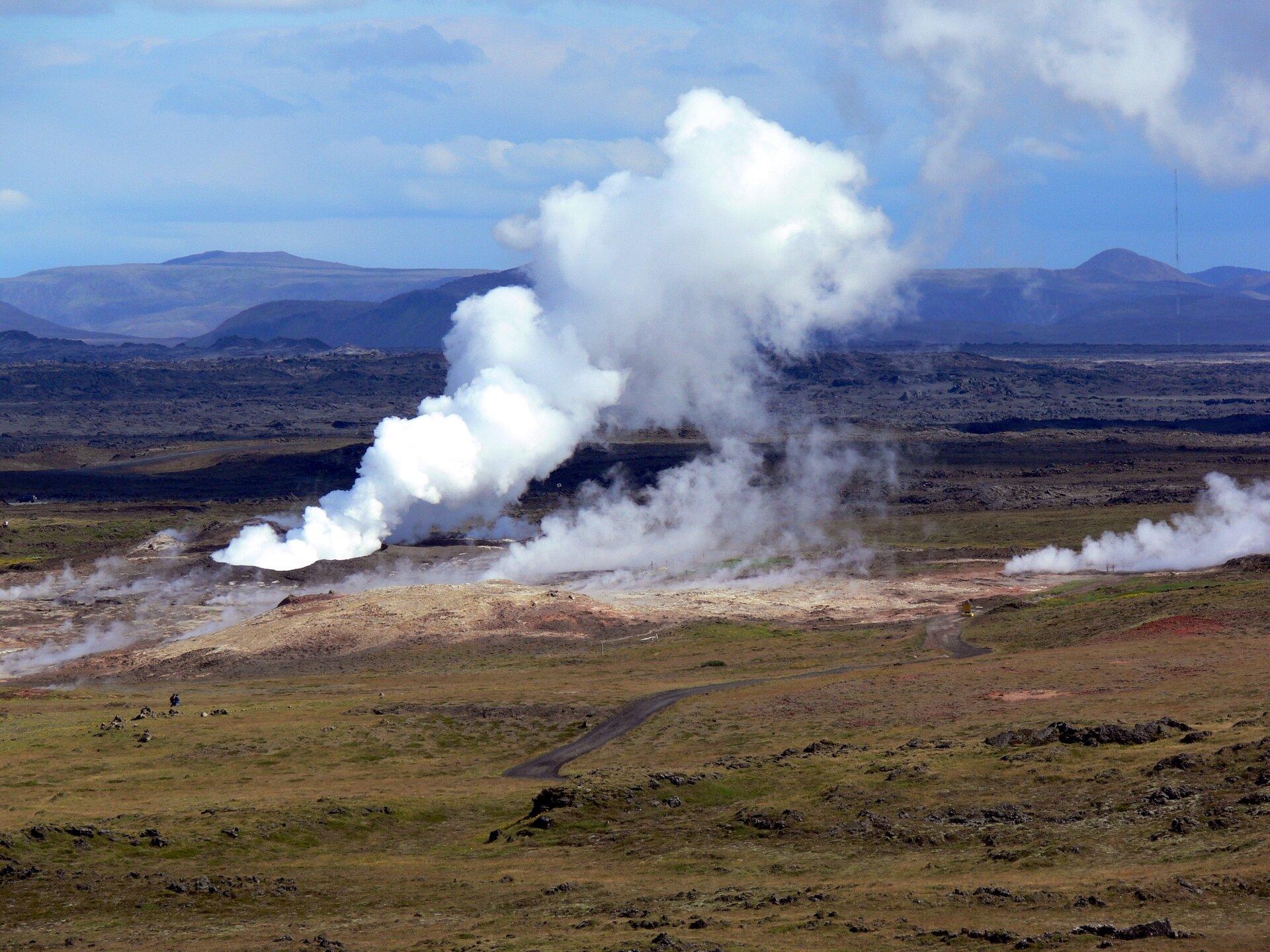 Na zdjęciu pofalowany teren porośnięty skąpą roślinnością, zkraterów wydobywa się biały dym. Wtle pasmo górskie.